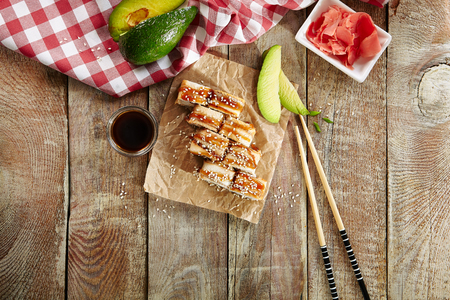 Salmon and Smoked Eel Sushi Roll with Pickled Daikon, Sauce, Sesame Top View. Photo of Nori Maki, Norimaki or Futomaki with Unagi and Raw Fish, Seaweed on Wooden Rustic Table