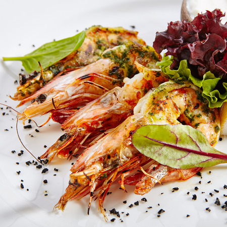 Hot Appetizer of Grilled Tiger Prawns with Green Oil on Elegant Restaurant Plate Isolated on White Background. Warm Starter with Fried King Shrimps with Herbs, Spices, Sauce, Lemon, Greens Close Up Banque d'images