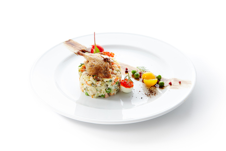 Olivier Salad or Russian Salad with Roasted Quail and Red Caviar on White Plate Isolated. Diced Potatoes, Carrots, Brined, Dill, Pickles, Green, Peas, Eggs, Onions, Mayonnaise and Spices Banque d'images