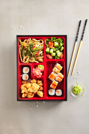 Fresh Food Portion in Japanese Bento Box with Sushi Rolls, Salad and Main Course Top View. Asian Style Lunch Box with Nori Maki Set, Meat, Cooked Vegetables, Rice Noodles, Pickled Ginger and Wasabi Stock Photo