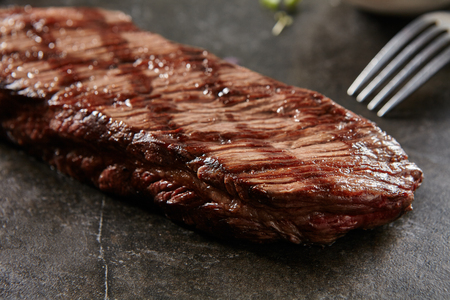 Hot Grilled Whole Denver Steak on Black Stone Background. Fresh Juicy Medium Rare Beef Grillsteak. Barbecue Meat Close Up
