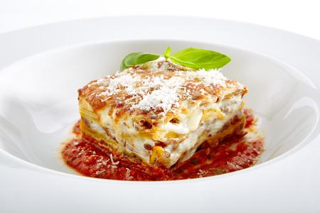 흰색 배경에 고립 된 토마토 소스와 함께 전통적인 수 제 이탈리아 라자 냐. 우아한 레스토랑 접시에 파마산 치즈를 곁들인 뜨거운 맛있는 라자냐 또는 라자냐 클로즈업