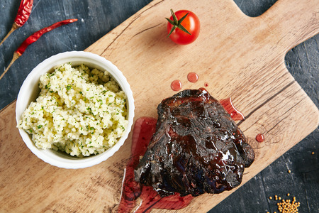Beef Cheeks with Red Berry Sauce and Couscous Close Up Top View. Hot Grilled Veal Tenderloin on Rustic Wooden Background with Spices and Garnish of Wheat Grains