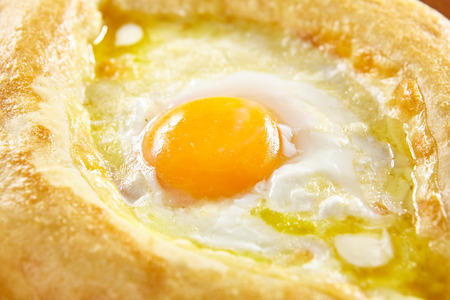 Homemade Ajarian Khachapuri with Sulguni Cheese Filled with a Raw Egg and Melted Butter Close Up.