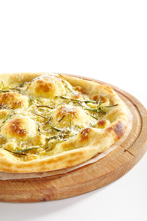 Thin Crispy Focaccia with Mozzarella, Rosemary, Grated Parmesan Cheese, Butter, Greens, Basil Oil on Wooden Plate Top View. Banco de Imagens