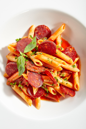 Italian Pasta with Salami, Cold Smoked Tomatoes, Onion, Garlic, Fresh Basil, Parsley, Sweet Chili Sauce, Bulgarian Pepper Close Up Reklamní fotografie - 124877107