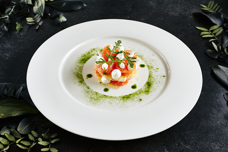 Beautiful Serving Italian Cuisine Dish of Salmon Millefeuille with Cream Cheese Mousse, Arugula and Capers. Archivio Fotografico - 126330121