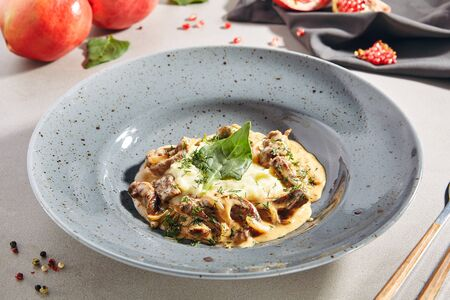 Classic Russian beef stroganoff or beef stroganov with mashed potatoes, mushrooms and greens close up. Restaurant main course with befstroganov in sour cream sauce or smetana, selective focus Reklamní fotografie
