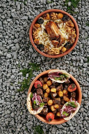 Set of Two Asian Dishes with Lyavangi and Jiz-biz in Natural Ceramic Bowls on Rustic Background Top View. Roasted Quail with Rice and Grilled Liver, Heart and Lungs with Potatoes on Gravel Texture Banco de Imagens