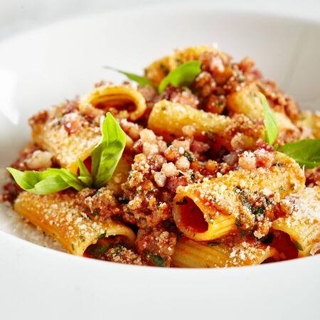 Assiette de restaurant blanche exquise de rigatoni maison avec sauce bolognaise et poitrine de porc fumé. Tubes de pâtes Penne italiennes de cuisine haute élégante sur fond de marbre noir naturel