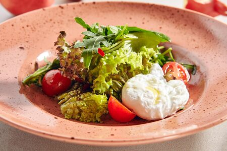 Salad with fresh vegetables and poached eggs close up. Macro photo of egg salat with arugula, lettuce leaves, cherry tomatoes and oil on elegant restaurant plate Banque d'images