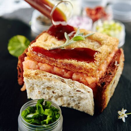 Restaurant Cold Starter Food - Delicious Fish Tartare with Spicy Sauce. Gourmet Restaurant Appetizers Menu. Fish Tartare Garnished with Crispy Bread Banque d'images
