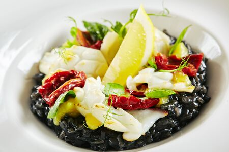 Exquisite Serving White Restaurant Plate of Black Risotto with Octopus and Sun Dried Tomatoes. Delicacy Cuttlefish or Squid Meat with Greens and Lemon on Natural Black Marble Background