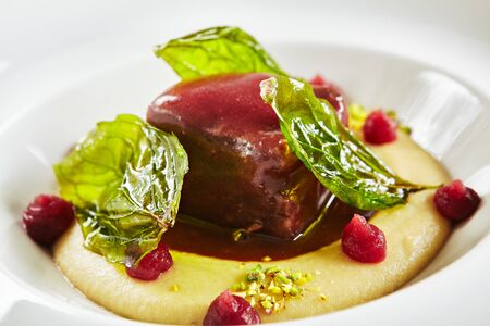 Exquisite Serving White Restaurant Plate of Beef Cheeks in Cherry Glaze with Potato-Celery Cream and Sauce of Dried Berries Closeup. Elegant Molecular Dish with Veal Fillet on Dark Stone Background