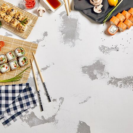 Japanese sushi rolls set with salmon and cream cheese and hot deep fried on bamboo napkin with chopsticks and cherry tomatoes with soy sauce and ginger on white rustic copyspace background
