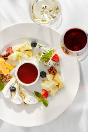 Gourmet, restaurant, delicious dinner food - close up of cheese plate with honey dip and fresh berries 스톡 콘텐츠