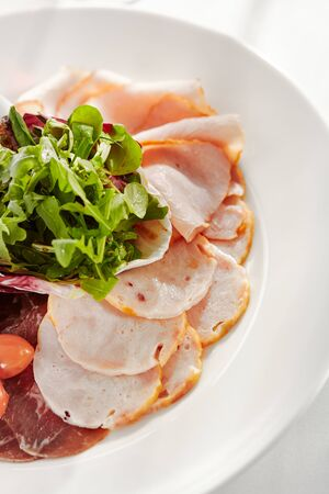 Gourmet, restaurant, delicious dinner food - close up of Sliced Meats with Rocket Salad and Tomatoes Stock Photo