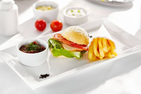 Gourmet, restaurant, delicious dinner food - close up of Sandwich with Smoked Meat, Tomato and Cucumber. Garnished with French Fries and Vegetables Sauce Stock Photo