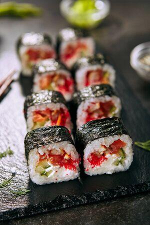 Macro photo of dragon roll with cream cheese, salmon, eel, rice, cucumber, flying fish caviar and nori. Dragon unagi maki rolls with raw red fish and tobiko on natural dark stone background close up Stock Photo - 129168998