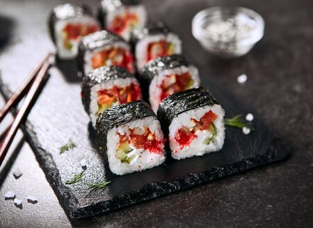 Macro photo of dragon roll with cream cheese, salmon, eel, rice, cucumber, flying fish caviar and nori. Dragon unagi maki rolls with raw red fish and tobiko on natural dark stone background close up Stock Photo - 129169543