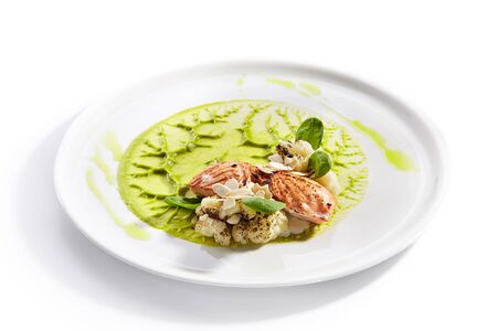 Salmon steak on plate close up. Red fish piece with green pea puree and cauliflower. Tuna with creamy sauce and vegetables isolated on white background. Restaurant tasty dish, cooked healthy meal 写真素材