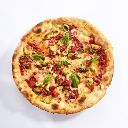 Vista superior de la pizza de mariscos. Cocina tradicional italiana en lonchas con carne de calamar y mejillones. Plato de restaurante pizzería aislado sobre fondo blanco. Ingredientes de mariscos en concepto de masa horneada