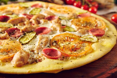 Homemade pizza on wooden table top view. Chicken meat, pickles, tomatoes slices and cheese ingredients on dough composition. Traditional Italian cuisine concept. Tasty baked snack, cooked meal