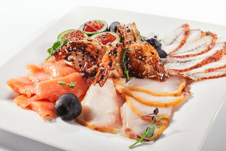 Fish platter with pink salmon, grilled eel, oil fish balyk and red caviar on elegant restaurant plate isolated on white background. Exquisite serving thin slices of salted and dried delicious seafood 写真素材