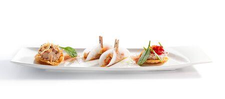 Taco con assorti de mariscos de cerca. Plato tradicional mexicano. Tortilla de trigo con rellenos de mariscos en un plato. Se sirven deliciosos bocadillos. Composición de aperitivo aislado sobre fondo blanco. Foto de archivo