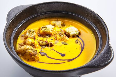 Pumpkin soup with croutons and strachatella closeup. Homemade dish, rustic cuisine. Autumn season, thanksgiving food isolated on white background. Tasty vegetarian dinner, delicious meal closeup