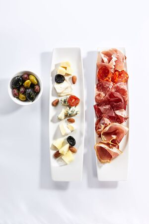 Antipasti on plates top view. Cheese and meat platter. Green and black olives in bowl isolated on white background. Appetizer, food starters concept. Served delicious snacks composition