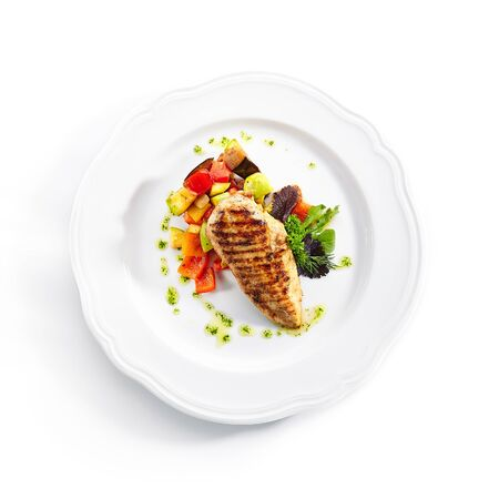 Top Viewt of grilled chicken fillet with side dish of baked vegetables on white restaurant plate isolated. Bbq chicken breasts or white meat barbecue with fried zucchini and bell pepper topview Фото со стока