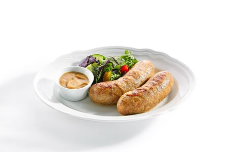 Macro shot of Bavarian sausages for frying with mustard sauce and mixed salad isolated. Traditional German rostbratwurst, wurst or bratwurst with fresh lettuce, rucola and chard leaves closeup