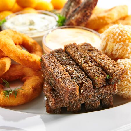 Beer snacks or beer plate with fried onion rings, squid rings, crisp cheese balls, potato croquettes, garlic croutons, deep-fried smelt fish with tartar sauces and a thousand islands dressing