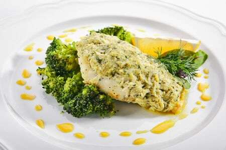 Macro shot of pike perch or zander fillet in cream sauce with broccoli isolated. Restaurant main course with fried sander fish or pike meat with lemon and greens closeup