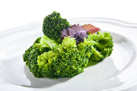 Macro shot of steamed broccoli on white restaurant plate isolated. Green asparagus cabbage cooked on steam, healthy veggie vegetables in vegan restaurent closeup