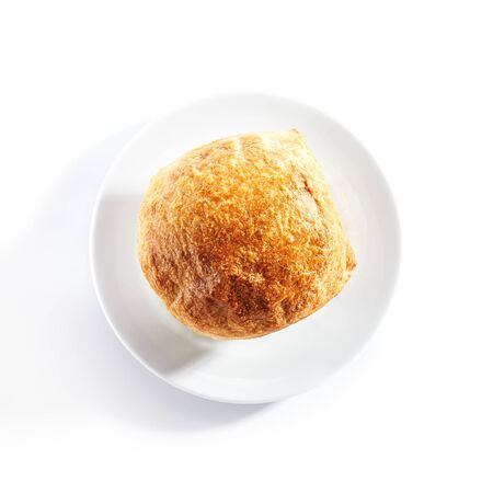 Top view of julienne or potage soup with chicken and mushrooms topped with melted cheese or puff pastry on white restaurant plate isolated.