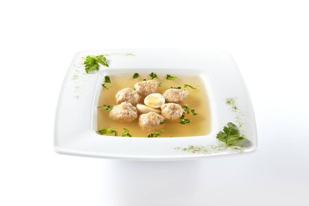 Macro shot of chicken soup with meatballs decorated with boiled quail egg and greens in square restaurant plate isolated. Imagens