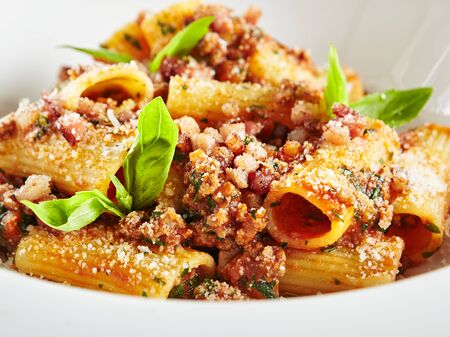 Exquisite Serving White Restaurant Plate of Homemade Rigatoni with Bolognese Sauce and Smoked Pork Belly Close Up.