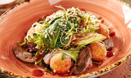 Menu de démarrage du restaurant de salade de magret de canard avec des boules de pommes de terre croustillantes sur un style rustique