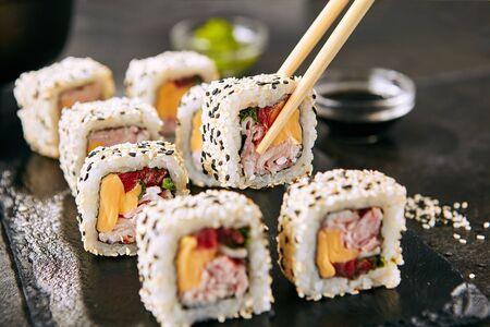 Chopstick holding rainbow uramaki sushi rolls with rice, bacon, processed cheese, tomato, green onion, sesame and nori on black slate plate
