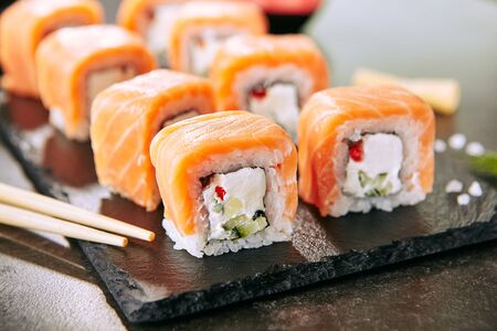 Beautiful Philadelphia Sushi Rolls Set with Salmon and Cream Cheese and Cuccumber on Black Slate Plate Close Up.