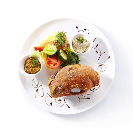 Top view of pork knuckle or pork shank baked with vegetables and mustard on white restaurant plate isolated. Grilled golonka, ham hock or eisbein with horseradish, vegetables and herbs topview 写真素材