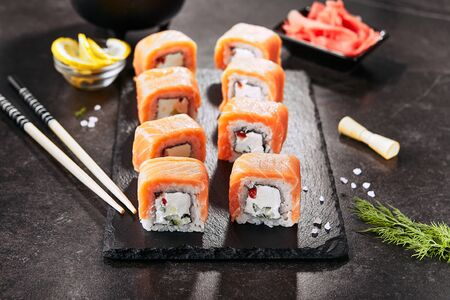 Beautiful Philadelphia Sushi Rolls Set with Salmon and Cream Cheese and Cuccumber on Black Slate Plate Close Up. Uramaki, Nori Maki or Futomaki Sushi with Trout Fillets, Soy Sauce and Wasabi