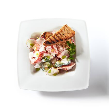 Rustic salad made of radish, cucumber and tomatoes with sour cream and rye croutons isolated on white background. Fresh summer vegetable salat with toasted bread topview