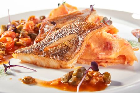 Pike perch or zander fillet with a side dish of tomatoes and capers served on a round platter. Restaurant main course with fried sander fish or barbecue pike meat on white plate isolated Stock fotó