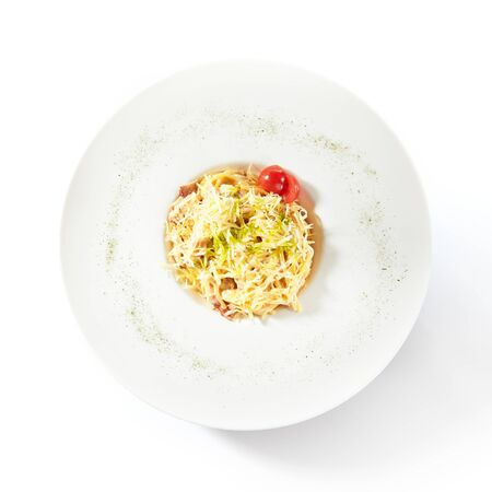 Delicious spaghetti carbonara with grated parmesan cheese isolated. Exquisite white restaurant plate of classic italian egg pasta with fried bacon and fresh tomatoes top view