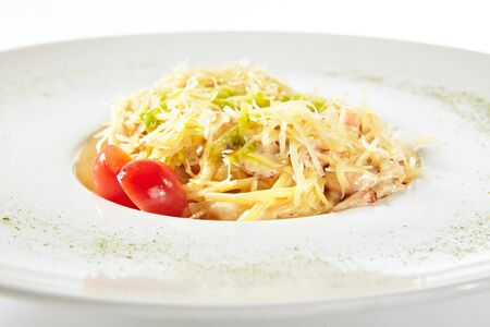 Delicious spaghetti carbonara with grated parmesan cheese isolated. Exquisite white restaurant plate of classic italian egg pasta with fried bacon and fresh tomatoes close up
