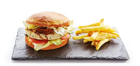 Fresh Chicken Burger with Onions, Tomato Sauce, Pickled Cucumbers, Green Lettuce, Turkey, Cheese and French Fries Garnish. Hamburger or Chickenburger on Natural Black Stone Plate Isolated on White