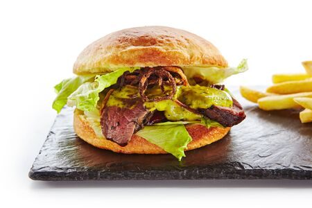 Classic Roast Beef Burger with Mustard, Fried Onions, Lettuce, Green Salsa Verde Sauce and French Fries Garnish. Beefburger with Medium Rare Steak on Natural Black Stone Plate Isolated on White